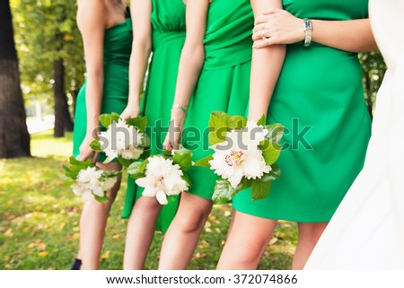bridesmaids in green dresses with white bouquets in hands - stock photo