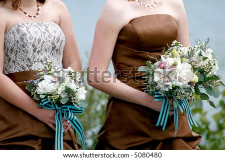 Bridesmaids standing at the wedding ceremony holding bouquets. - stock photo