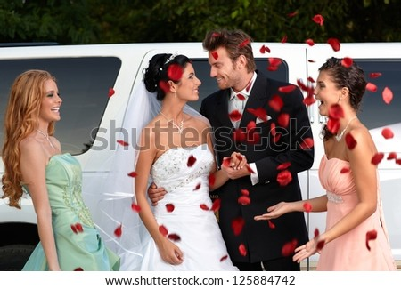 Bridesmaids throwing rose petals on young couple. - stock photo