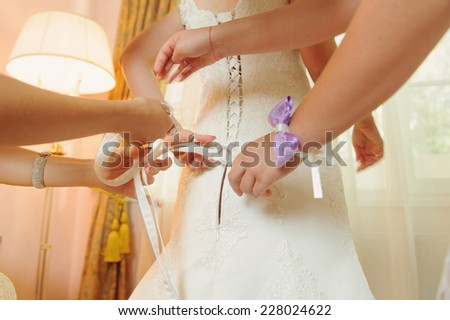 bridesmaids tying bow on corset of wedding dress - stock photo