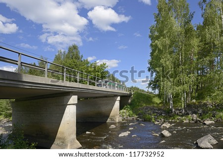 Bridge across northern river with rapids - stock photo
