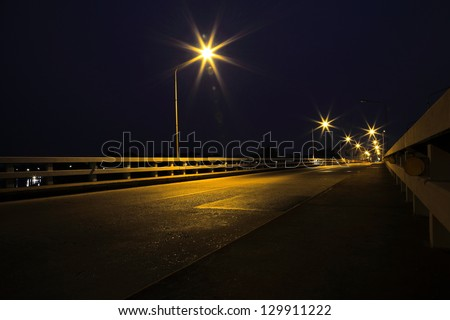 Bridge across the river at night in Ubon Ratchathani, Thailand.(Mun River) - stock photo