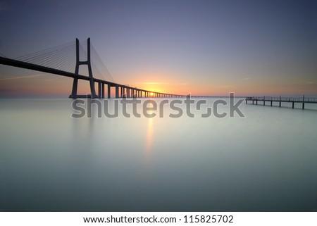 Bridge and pier at sunrise - stock photo