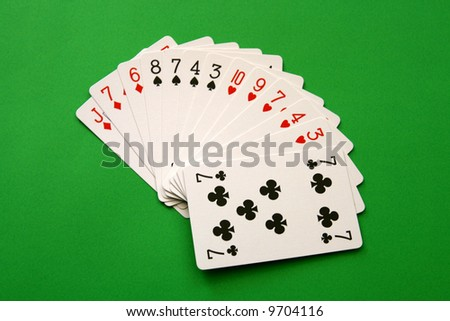 bridge cards - one hand (8,7,4,3 spades, 10,9,7,4,3 hearts, J,7,6 diamonds, 7 club)  background green, - stock photo
