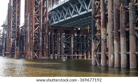 Bridge construction. Rusty metal piers of the unfinished bridge across the Dnieper in Kyiv (Ukraine).