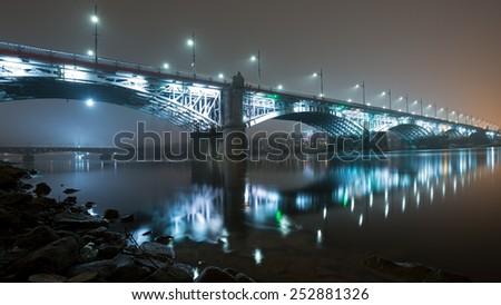 Bridge illuminated at night in the fog. Poniatowski Bridge - stock photo