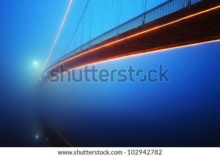 Bridge in a foggy night - stock photo