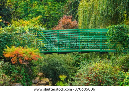 Bridge on a path in a flower garden - stock photo