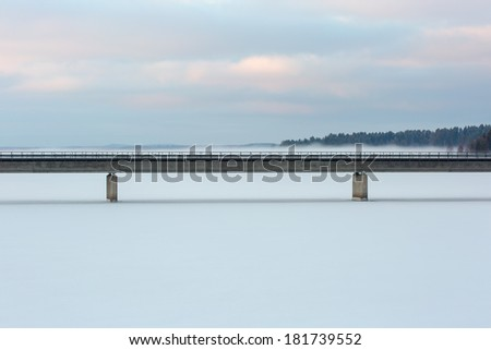 Bridge over a frozen lake on a cold frosty morning with fog in the background - stock photo