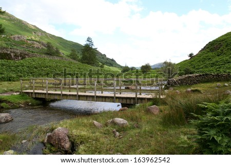 Bridge over a mountain stream in the Cumbrian Mountains of England's Lake District National Park. - stock photo