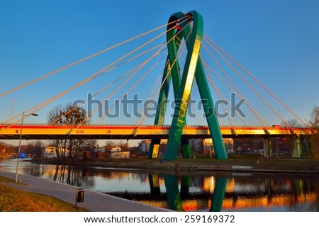 Bridge over a river. Cable stayed bridge over Brda river at sunset in Bydgoszcz City, Poland. - stock photo