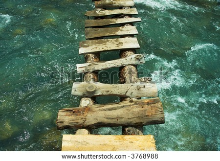 bridge over rapid mountain river - stock photo