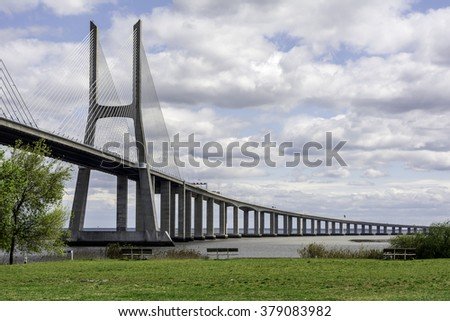 Bridge over the river in Lisbon, Portugal - with water and grass and the cloudy sky. Vasco da Gama. - stock photo