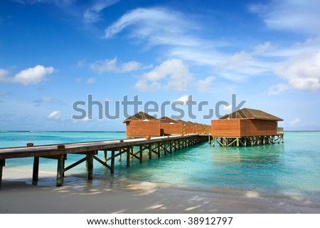 bridge over tropical ocean to water villas - stock photo
