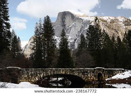 Bridge underneath the gaze of Half Dome, the dominant feature of Yosemite National Park. - stock photo