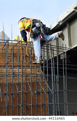 Bridge widening construction project: Workman climbs reinforcing bars used in concrete forms - stock photo