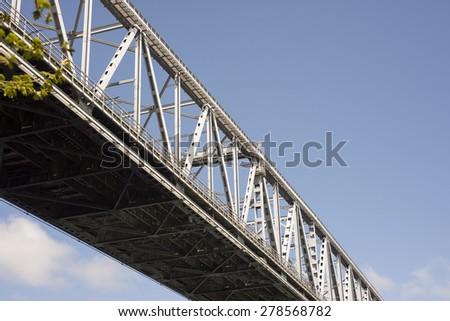 Bridge with bridge-walking bridge and small people in gray coveralls on top of the Old Little Belt Bridge. - stock photo