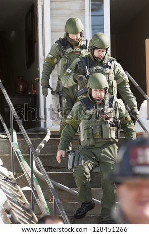 BRIDGEPORT, CT , U.S. -Â?Â? FEBRUARY 13 : Unidentified members of Bridgeport Police SWAT team exit a home after reports of a barricaded gunman in the residence on Roberts St. in Bridgeport, Ct. on February 13, 2013. - stock photo