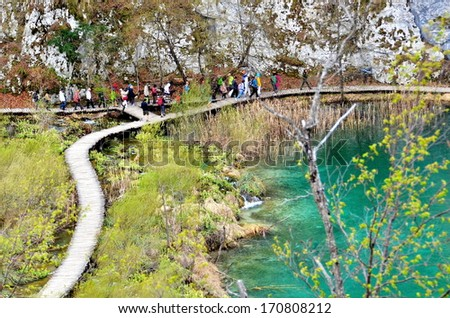 Bridges and wooden paths leading visitors between the rich colors and unique vegetation of the Plitvice Lake.    - stock photo