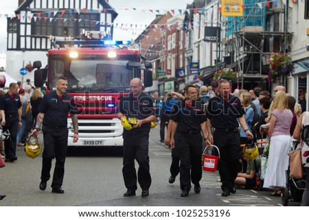 BRIDGNORTH, UK - JUNE 24: Firemen pass along the line of the watching public collecting charitable donations in their firemens helmets during the Bridgnorth carnival on June 24, 2017 in Bridgnorth