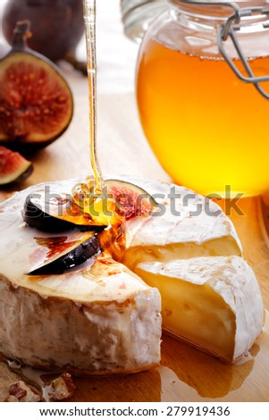 Brie Cheese and sliced Figs poured with honey on wood cheese-board - stock photo