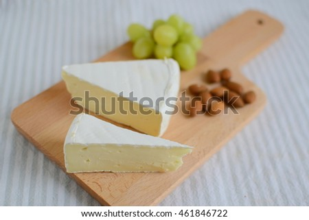Brie cheese in wooden plate