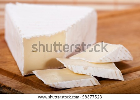 Brie cheese on cutting wood - stock photo