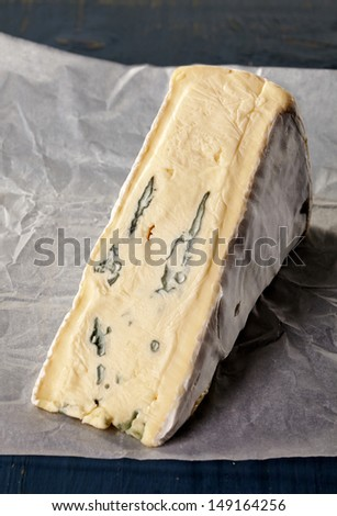 Brie cheese on white baking paper - stock photo