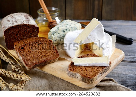 Brie cheese, rye bread slices, roquefort and honey on a cutting board - stock photo