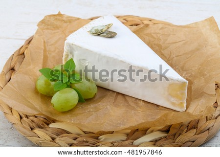 Brie cheese with grape on wood background