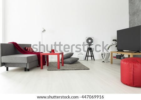 Bright and airy living room with grey furniture and red accessories - stock photo