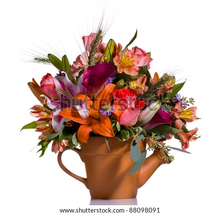 Bright and colorful bunch of flowers arranged in a watering can plant pot - stock photo