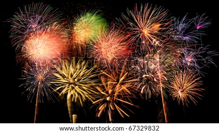 Bright and colorful fireworks against a black night sky - stock photo