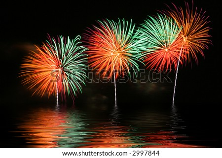 Bright and colorful fireworks display with reflection on water. - stock photo