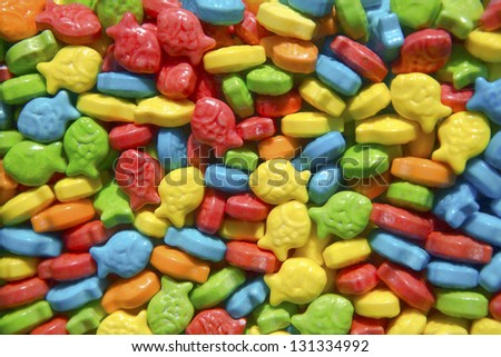 Bright and colorful fish shaped candies in a gumball dispenser. - stock photo