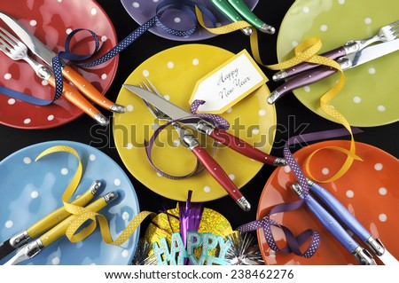 Bright and colorful Happy New Year party dinner table with red, yellow, orange, blue, green, and purple polka dot plates and cutlery. - stock photo