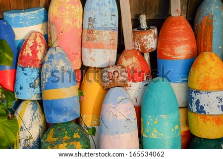 Bright and colorful lobster floats and lobster buoys in a small new england fishing village - stock photo