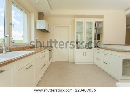 Bright and delicate kitchen in modern house - stock photo