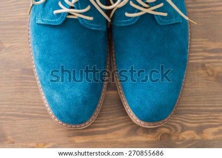 Bright aqua man's shoes with laces are on a wooden bench - stock photo
