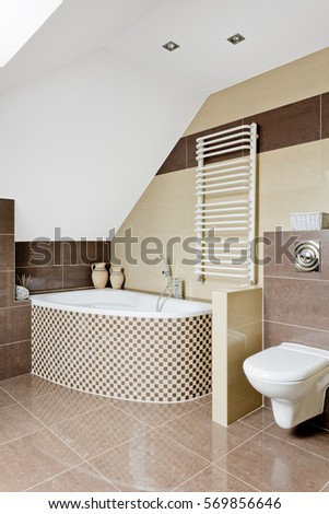 Bright attic bathrom with tiles, bathtub, toilet and radiator on the wall