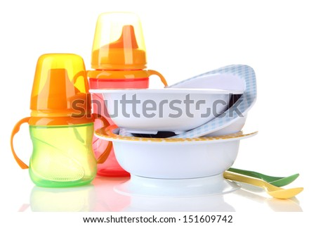 Bright baby bottles, bowls and spoons isolated on white - stock photo