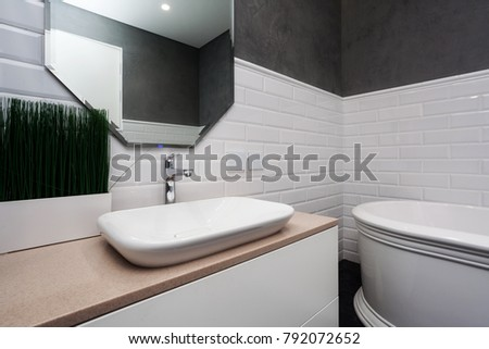 Bright bathroom with new tiles. New washbasin, white sink and large mirror
