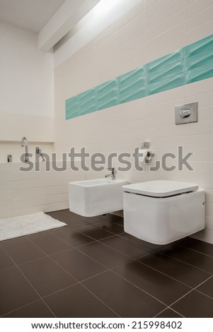 Bright bathroom with toilet and bidet, vertical
