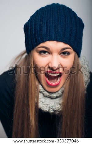 bright beautiful girl screaming in confusion, a photo studio, isolated on a gray background