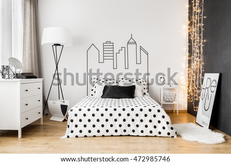 Bright bedroom interior with wide bed, commode and one black wall