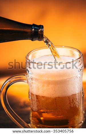 bright  beer is  poured into a glass mug - stock photo