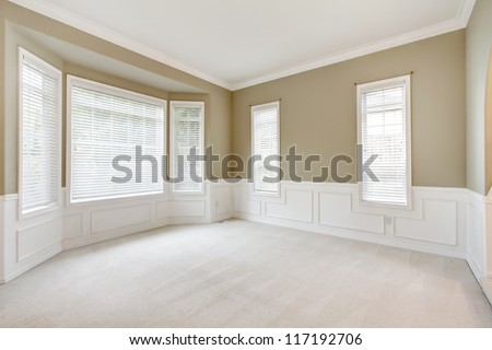 Bright beige large empty room with carpet, molding and  windows.