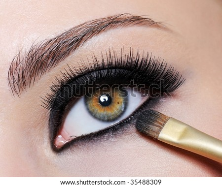 Bright black eye make-up on the close-up shot of female eye - long eyelashes - stock photo