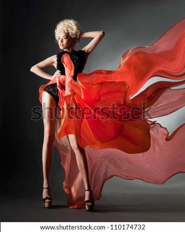 Bright blonde in fluttering red skirt - stock photo