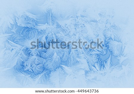 Bright blue frost pattern on a window glass in the winter (as an abstract winter background), retro style